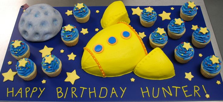 "Rocket Ship and Moon Cake - This is a cake my sister and I did for a little boy's birthday. The rocket ship and the moon are marble cake and the cupcakes are vanilla. All have vanilla buttercream frosting and the moon is also covered in fondant. The stars on top of the cupcakes and on the cake board are fondant.  The blue cake board is a foam core board.  Inspiration came from a similar cake I saw on Flickr.  The mom said the little boy just stared at it and said ""Wow""."