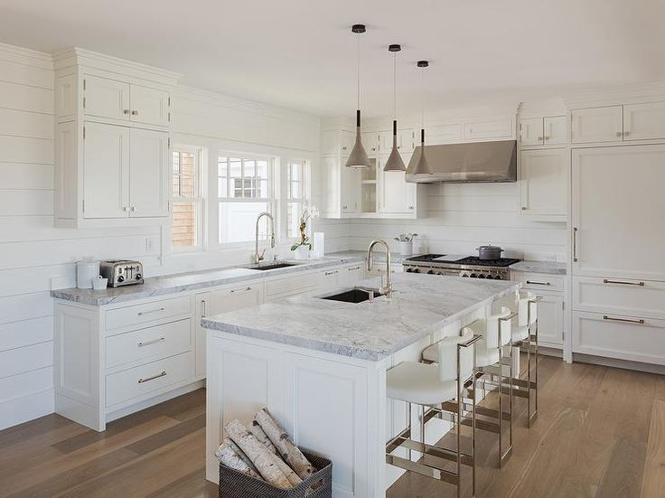 Chic white cottage kitchen features creamy white shaker cabinets paired with gray marble countertops and a shiplap backsplash.