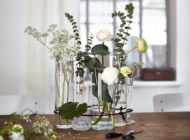 A romantic take on flower arranging with clear vases tied together with a piece of black twine.