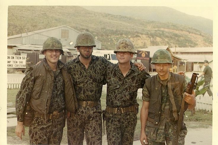 Four Marines pose for the camera. Three of them are ...