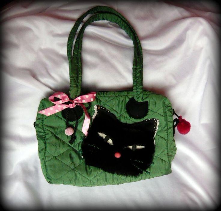 Cicás kislánytáska -Handmade by Judy Majoros: Steppelt anyagból készült ez a cicás táska. Vatelin és vetex ad tartást a táskának. Elején fekete műszőrméből készült cicafej, valamint rózsaszín pöttyös masni látható. Belseje pöttyös –virágmintás pamutvászonnal bélelt, egy zsebecske található benne. A cipzárt egy pink pom-pom díszíti.