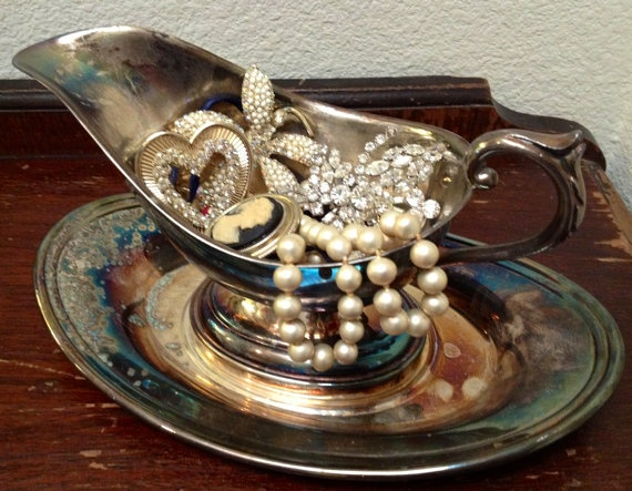 Cute display of vintage brooches and jewelry in a silver gravy boat on a silver platter.