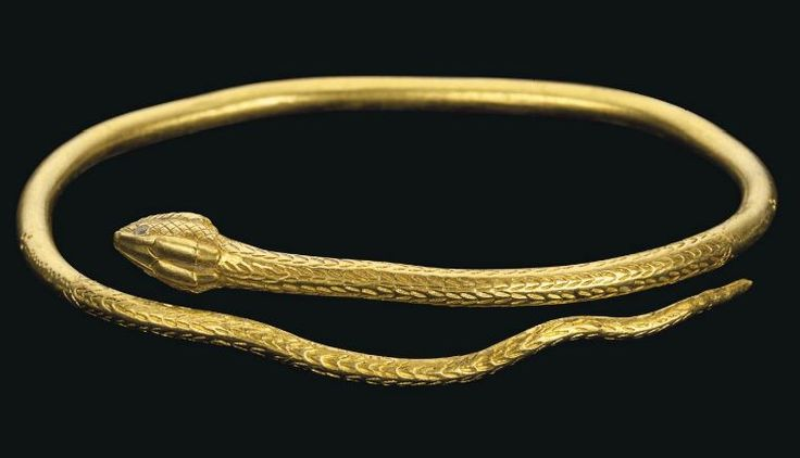 Roman gold snake bracelet, 1st century A.D. In the form of a snake, formed from a solid coiled wire, circular in section, the well-articulated head overlapping the tail, the dorsal and ventral scales defined by stamped chevron, three lines of incised dots extending from the scales on either side terminating in three dots, the finely detailed head with enamel eyes and an open mouth, 8 cm wide. Private collection