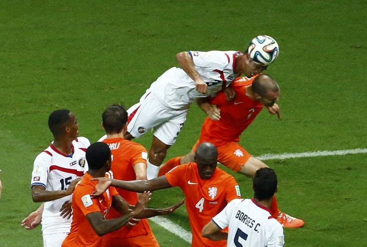 Costa Rica's Giancarlo Gonzalez jumps for the ball next to Ron Vlaar of the Netherlands during their 2014 World Cup quarter-finals at the Fonte Nova arena in Salvador July 5, 2014.