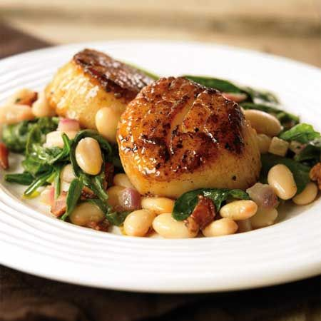 Seared Scallops with White Beans and Spinach     Scallops are an awesome source of lean protein, and are ridiculously easy to cook (around 6 minutes per scallop!). Combine them with white beans, spinach, and the secret flavor-packed ingredient, bacon, and you have a delicious dinner in a flash