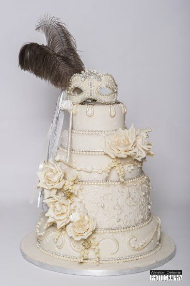 A masquerade wedding cake featuring a mask made of sugar and swarovski crystals as well as ostrich feathers on a pearlized ivory fondant. Cake: Ana Paz Cakes, Miami, FL... I love the masquerade mask as the topper!!