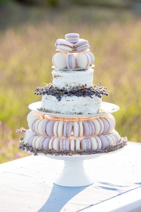 A buttercream cake decorated with lavender is elevated by the addition of pastel colored macaroons. #weddingcake #macaroons