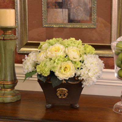 """Green Hydrangea Silk Floral Arrangement in Black Vase AR348 - Usher in the springtime with the soft green, white and yellow hues of a ranunculus and hydrangea bouquet. This smaller silk floral design comes in a black ceramic vase with gold accents and is perfect for an end table or accent table. Measures 11""""H x 11""""W x 9""""D"""
