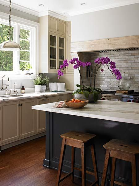 This version of a white kitchen feels less cold and more welcoming than most, with light wood and rustic stools