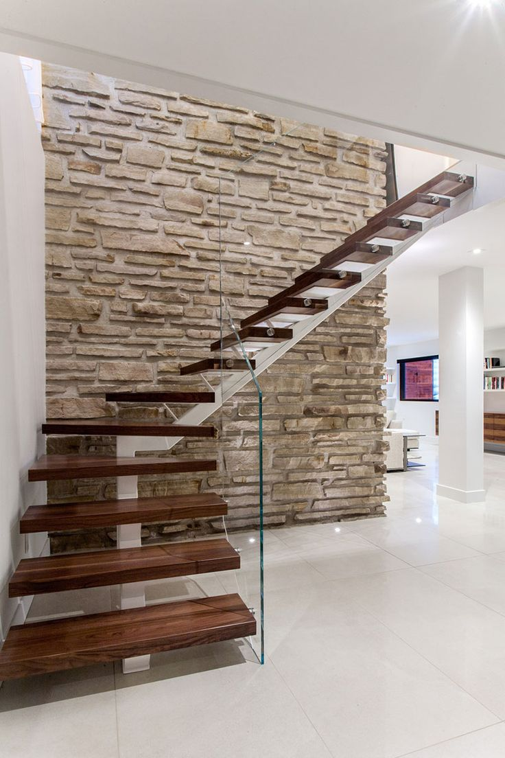 A beautifully designed staircase that blends old and new. The brick wall is actually the side of a 1950s chimney. The staircase uses thick wood slab treads that seem to float on the white painted steel stringer. Best of all, the transparent glass banister lets the beauty of the stairs shine through.
