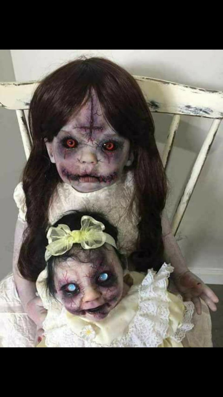 Two creepy dolls and one with the upside down cross on her little head