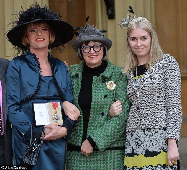 Prince Charles honors a Queen. Grayson Perry, an acclaimed potter (and acknowledged and very out transvestite), poses with his wife Philippa and their 21-year-old daughter Flo after Potter was presented the honor of CBE (Commander of the British Empire) by Prince Charles.