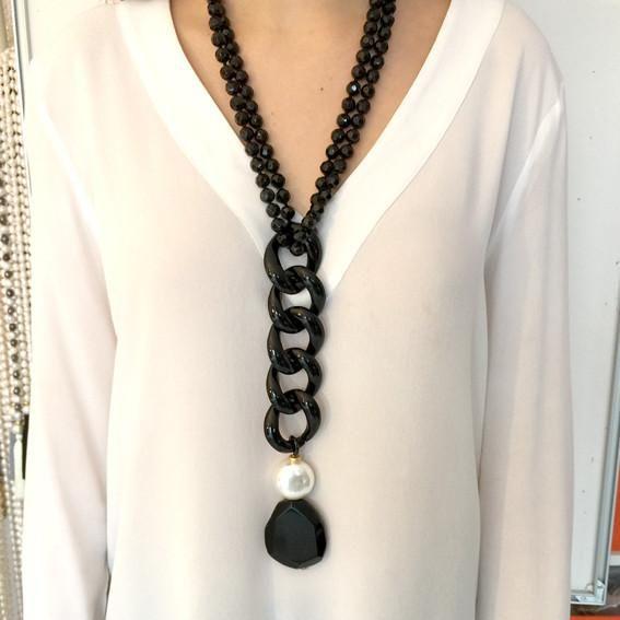 Collar de cadena de resina negra con perla de rio ó cristal de roca, terminada en perla de nacar con ágata negra. Cierre con cinta de grogué ajustable. Cuida