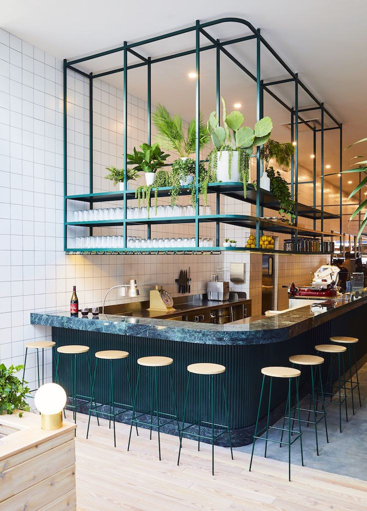 Restaurant in New York with pendant lighting made from hand-blown glass globes and brass arms, custom furniture like the long oak and marble tables to encourage communal eating, and private nooks for working.