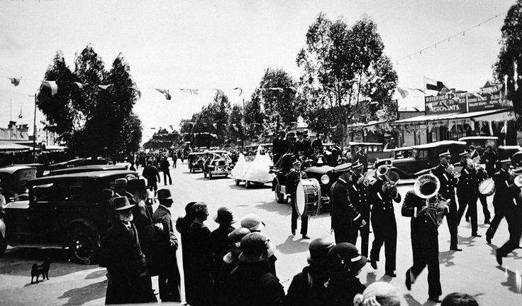 The street parade in the 'Back to Kaniva' celebrations. A brass band is marching down the street followed by decorated motorcars. Streamers hang across the street, c1935.