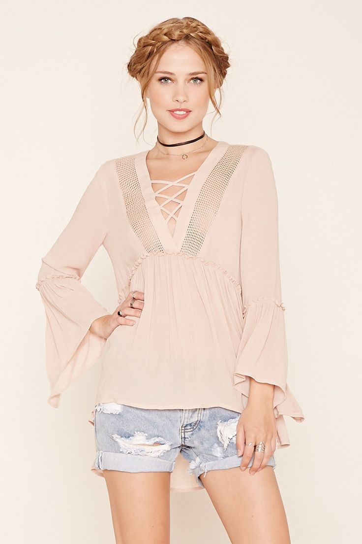 A woven trapeze top with long bell sleeves, a grid cutouts framing the crisscross neckline, and a slightly flared hem.