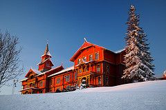 The Red Hotel in Winter (RobertCross1 (off and on)) Tags: trees winter sunset red snow oslo norway architecture hotel interestingness olympus polarizer omd holmenkollen holmenkollenparkhotelrica anawesomeshot microfourthirds 20mmf17panasonic