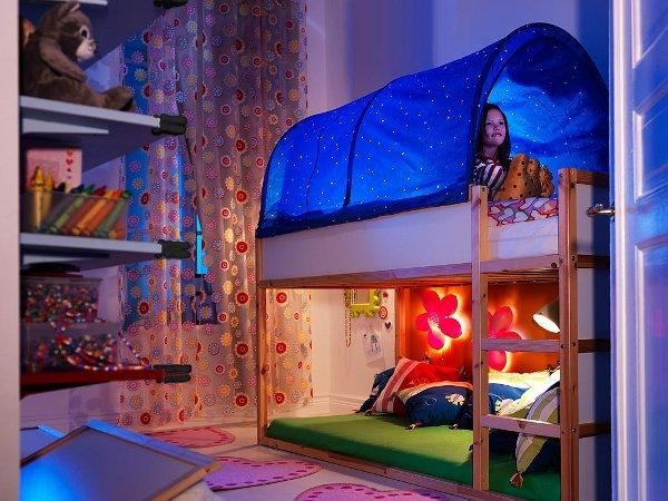 Make your kiddos feel like campers in their own room. Install a tent-like cover on top of the bunk. And place illuminating lamps and flowers on the bed side wall.