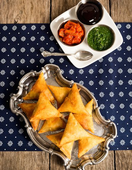 A plate of samosas - a vegetarian dish commonly found in Indian restaurants - with onion-tomato chutney, mint-coriander chutney and tamarind sauce for dipping.