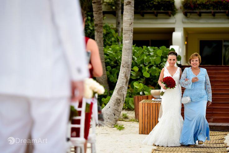 Blushing bride walks down the aisle with her mother during a wedding at @gvrivieramaya in the Mayan Riviera, Mexico. Photo courtesy of #DreamArtPhotography.