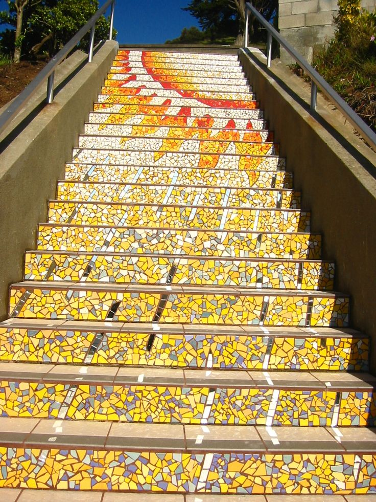 Tiled Yellow Mosaic of the Sun on the steps of an outdoor staircase in California.