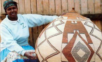 "Africa | Zulu basket weaver, Vina Ndwandwe, sitting next to one of her own creations | Image included in the publication ""Zulu Basketry"" by Jannie van Heerden"