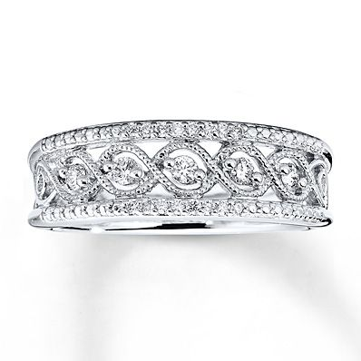 This lovely ring for her is embellished with interwoven ribbons of sterling silver flowing through the middle of the eye-catching design. Round diamonds are sprinkled throughout the band, for a total weight of 1/5 carat. Milgrain detailing completes the look. Diamond Total Carat Weight may range from .18 - .22 carats.