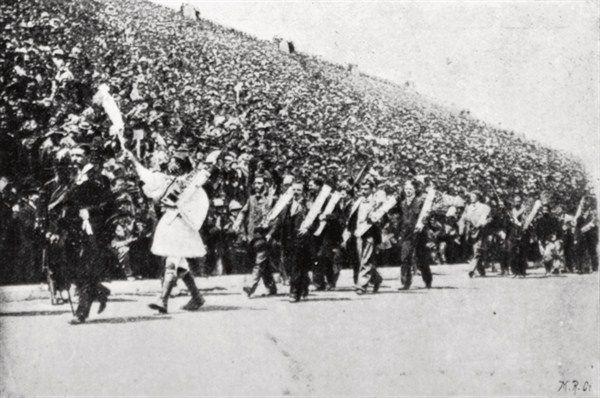 Η παρέλαση των νικητών κατά τη διάρκεια της τελετής λήξης, [15 April 1896] με πρώτους τον Κωνσταντίνο Μάνο και τον Σπύρο Λούη. Parade of the winners (1st and 2nd place) of the Olympic Games of 1894 during the closing ceremony in the Olympic Stadion in Athens. Spiridon Louis leads the parade