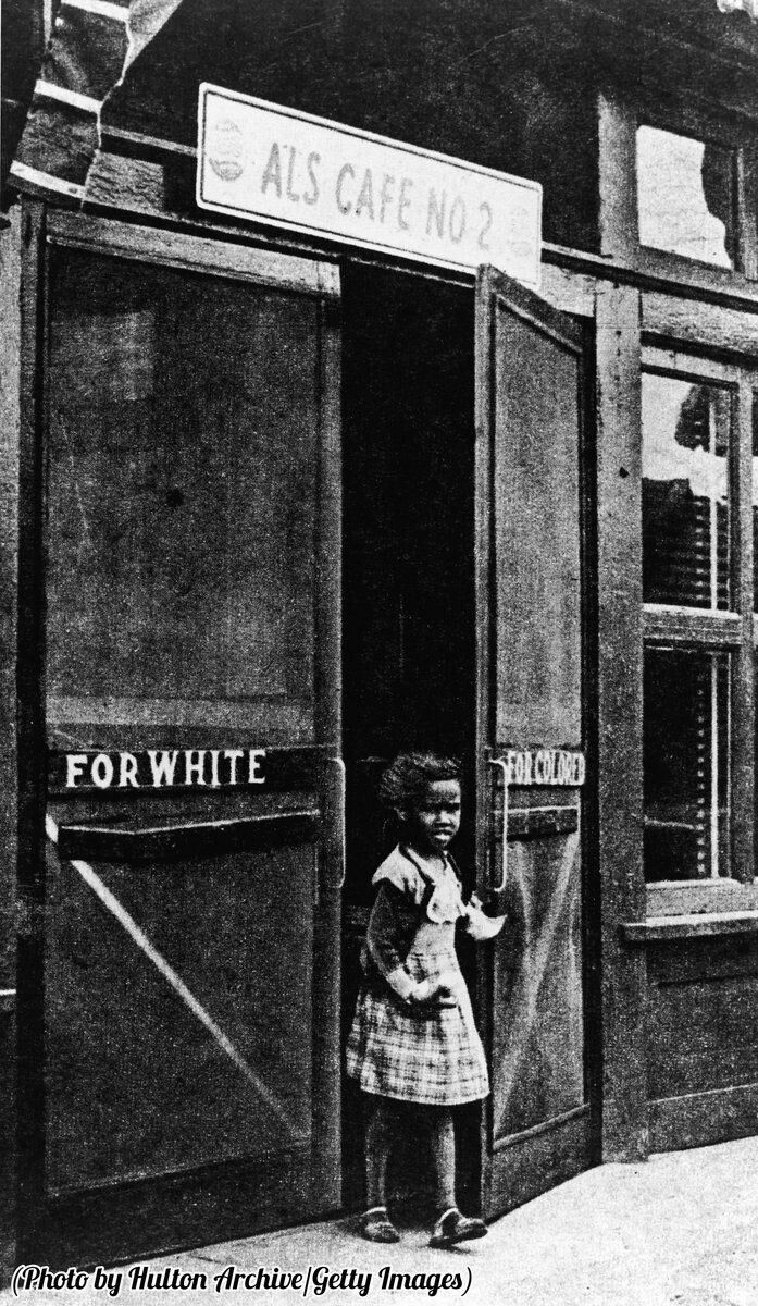 "Historygram: 🌎──────────── A girl leaves a cafe through a door marked ""For Colored"", circa 1950. 🇧🇷──────────── Uma menina deixando um café por uma porta escrita ""De cor"", cerca de 1950. 🇪🇸──────────── Una niña se va de una cafetería pasando por una puerta marcada como ""De Color"", cerca de 1950. 🇮🇷──────────── خروج دختری سیاهپوست از درب مخصوص رنگین پوستانِ یک کافه، حدود سال 1950  [ #hg_racism 
