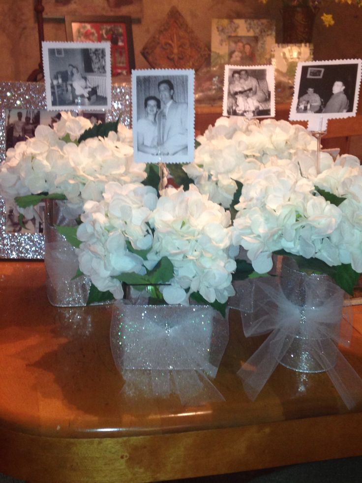 60th Anniversary party idea for table centerpiece.  Put a picture of the couple's engagement, wedding, etc., on a card stick in the middle of the flower arrangement. It personalizes it and looks amazing!