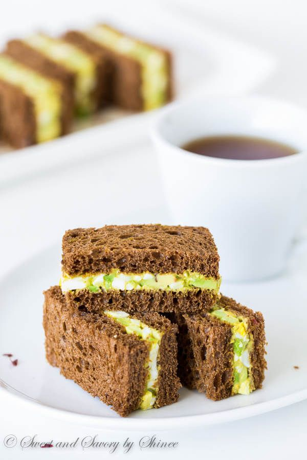 Spicy avocado egg salad sandwiched between chewy pumpernickel bread slices. Perfect texture contrast and flavor combination! #Tea #TeaTimeFood