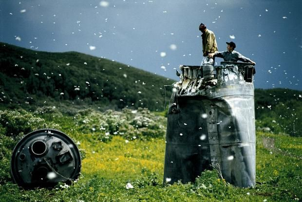 Jonas Bendiksen  RUSSIA. Altai Territory. 2000. Villagers collecting scrap from a crashed spacecraft, surrounded by thousands of white butterflies. Environmentalists fear for the region's future due to the toxic rocket fuel.