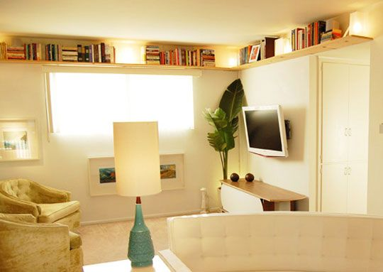 We can part with our CDs, thin out our closets of clothing, stop coming home with curbside finds...but we must find more room for more books [wild eyed]. Laure's Book in the Rafters idea and the wrap around ceiling shelving shown above are both efficient uses of overhead space.