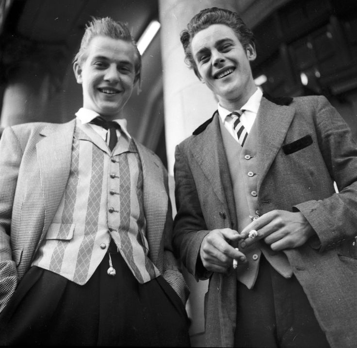 Teddy boys were known as the bad boys in London 1950s. These lads dressed with an Edwardian inspiration. They wore 3 piece (and more) suits. Usually wore drape jackets, paired with some slim-fit pants, exposing the socks. Their suits had velvet trimmings, and they accessorized with slim jim or western ties. Shoes where oxfords or brogues.