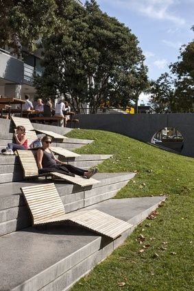 Hurstmere Green, Auckland. Bleachers with lounge furniture and interesting triangular insertion into mound of earth.