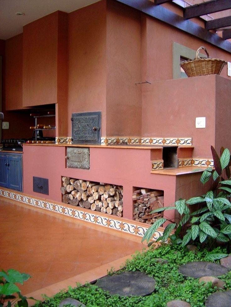 """A cozinha externa e rústica, pensada pela arquiteta Paula Gambier, conta com fogão a lenha, forninho com tampa de ferro trabalhada e churrasqueira dispostos em linha. Os tozetos de ladrilho hidráulico e a pintura terra cal reforçam o estilo """"caipira"""" do espaço"""