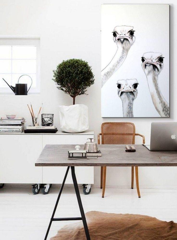 bureau scandinave aménagé avec une table en bois grisâtre à piétement en métal, un tapis en peau de vache et un tableau autruches curieuses