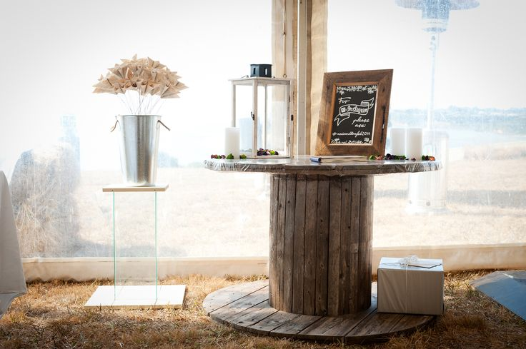 Rustic wedding. Present table. Wooden cable drum. instagram tag request. Tin buckets, Glass plinth. Handmade paper flowers.
