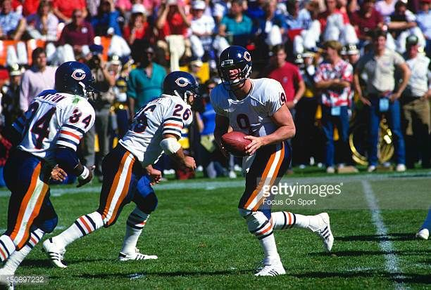 Quarterback Jim McMahon of the Chicago Bears turns to hand the ball off to Walter Payton against the San Francisco 49ers during an NFL football game...