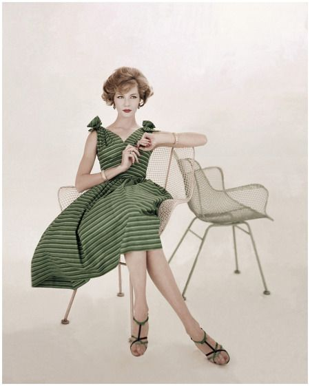 Model Jessica Ford.    wearing striped sun dress with bows at shoulders by Rhea, sandals by I. Miller, seated in patio chair 1958 Condé Nast Archive/Corbis.    Photo Karen Radkai.