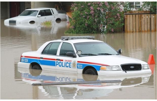 A city police car sits abandoned in flooded Sunnyside on Friday morning June 21, 2013. Photograph by:  Read more: http://www.calgaryherald.com/Gallery+Pictures+from+flood+ravaged+Alberta/8559569/story.html#ixzz2WteCyfO9