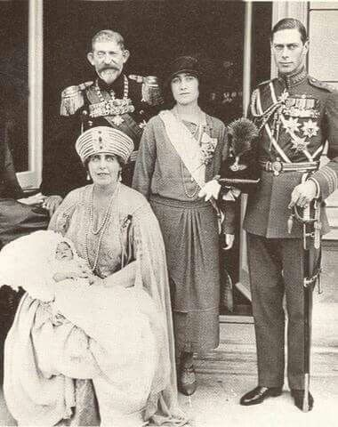 Queen Marie of Romania holding her grandson, the future King Peter II of Yugoslavia, her husband Ferdinand of Romania, with the then Duke and Duchess of York