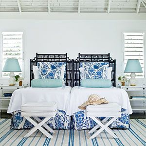 The iron gated headboard makes this coastal bedroom feel more like a luxe boudoir.