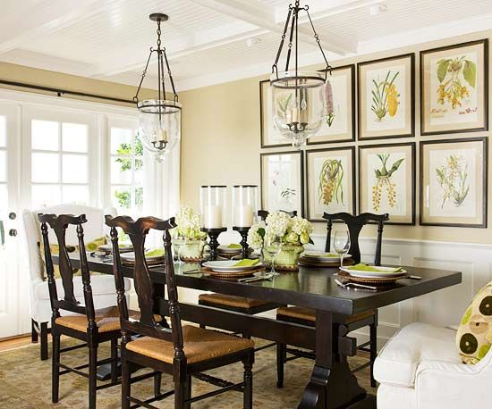 Large botanical prints fill an otherwise plain wall. White upholstered chairs with printed accent pillows at each end.