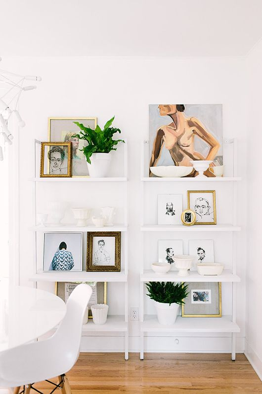2. LAYER WALL ART ON BOOKSHELVES I love the idea of displaying wall art on shelves or a bookcase that is the same color as the wall. It adds depth to the grouping while still allowing the artwork to shine, and enables you to easily rearrange and include decorative accessories for an interesting yet casual display. (image by Jennifer Young via SF Girl By Bay)