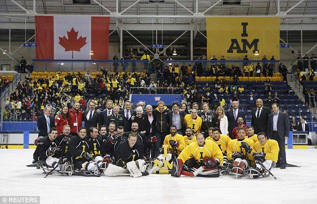 Harry, Justin andToronto Mayor John Tory pose with officials and sledge hockey players during the Invictus Games launch