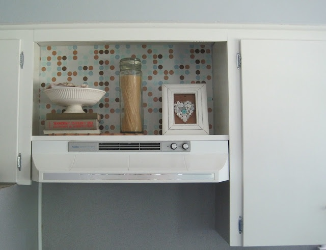 Love this idea...leave the cabinet doors off above the stove...put some decorative contact paper up to add some visual interest in the kitchen!