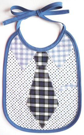 Bavoir Chemise Cravate Bleu en Coton et Plastique pour les Garçons tissu à carreaux, vichy et pois Les Bavoirs Bibi Pirouette sont tous couverts sur le devant d'un plastique transparent et résistant permettant d'être nettoyés très facilement d'un coup d'éponge. Bavoir imitant une chemise à pois noir avec col de chemise et poche en vichy bleu, ainsi qu'une cravate à carreaux bleu.