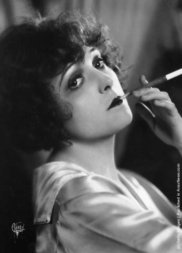 Madge Bellamy, the stage name of Margaret Philpott (1899–1990) the American general purpose actress of the 20s. She was a former dancer and beauty queen. Pictured in languid pose, smoking a cigarette, using a long cigarette holder, ca. 1928.