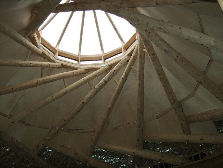 This is not a typical reciprocal structure. It was constructed in the usual way but additional braces were added to allow the original ring to be cut away. This left a larger space for the window, or in this case a pyramid of windows to shed the rain more effectively. This is one of the buildings at Hill Holt Wood where they teach reciprocal roof building http://hillholtwood.com/